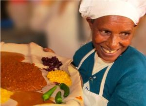 Cafe manager, Shitye, joyfully serving up a beautiful Beyaynetu dish